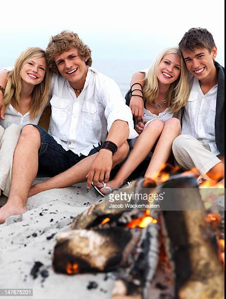 Grupo de adolescente parejas de estar juntos en la playa con fogata