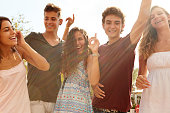 Group Of Teenage Friends Dancing Outdoors Against Sun Smiling