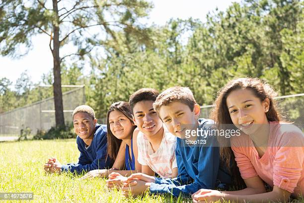 Group of teenage friends hang out together at park, campus.