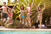 Group Of Teenage Friends Jumping Into Swimming Pool Smiling