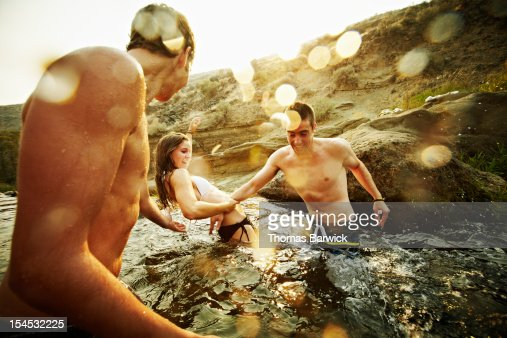 Group of teenage friends playing in water : Stock Photo