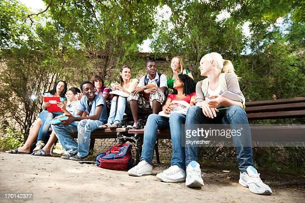 Gruppe von teenage Freunde sitzen auf der Bank.