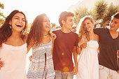 Group Of Teenage Friends Walking Along Street Laughing