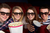 Group Of Teenage Friends Watching 3D Film In Cinema