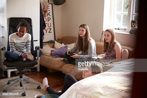 Group Of Teenage Girls Playing Video Game In Bedroom