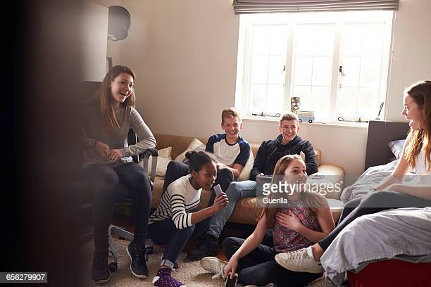 Group Of Teenagers Hanging Out In Bedroom Together