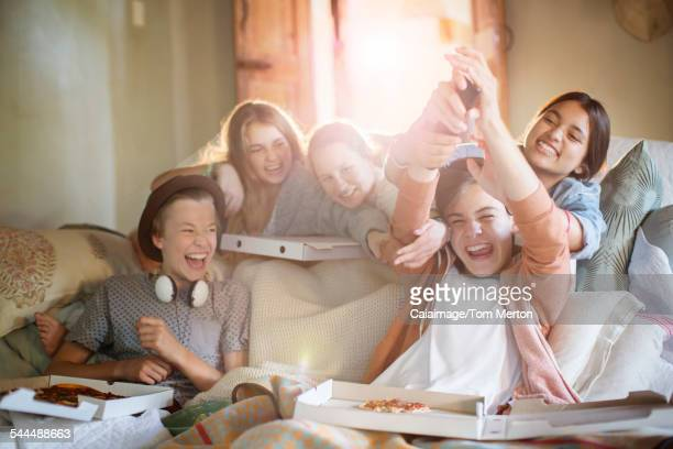 Group of teenagers having fun while watching tv on sofa