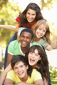 Group Of Teenagers Having fun Piled Up In Park