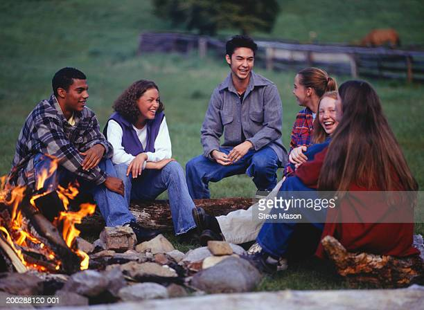 Group of teenagers (14-15) (16-18) sitting around campfire in country field