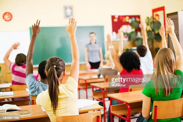 Gruppe von Teenagern, die im Klassenzimmer sitzen und heben die Hände.