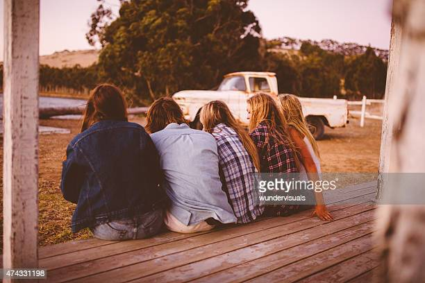 Group of teenagers sitting on a porch talking