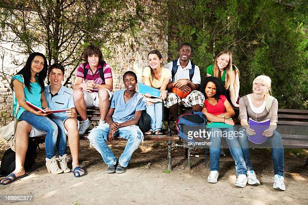 Group of teenagers sitting on bench outdoors
