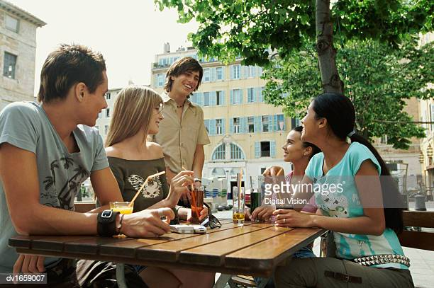Group of Teenagers Sitting With Drinks at a Table in a Pavement Cafe