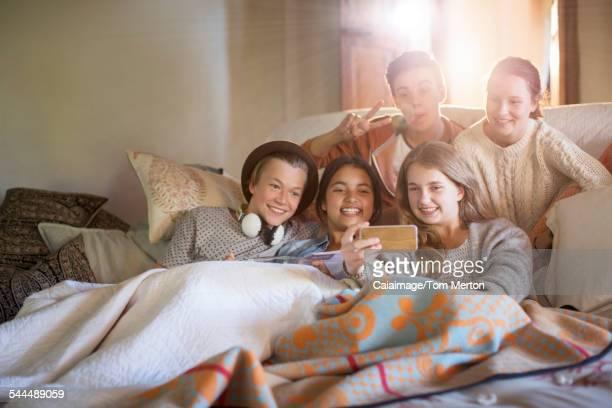 Group of teenagers taking selfie on sofa in living room