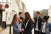 Group Of Teenagers Walking Along Street In Urban Setting
