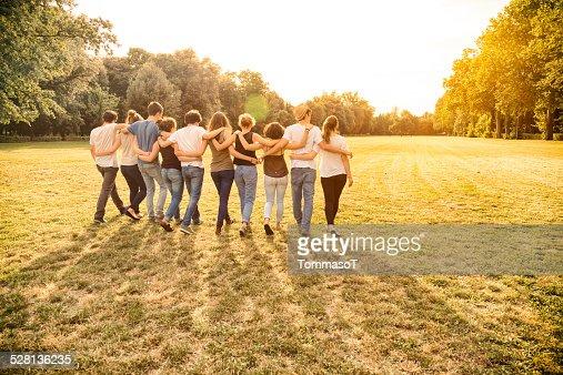 ティーンエイジャーのグループで歩く一緒での保持