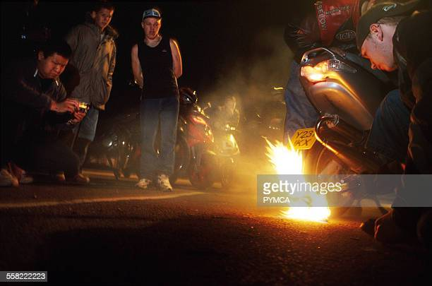 A group of teenagers watching a Catherine Wheel stunt scooterists Luton UK 2004