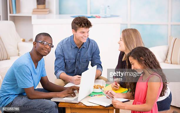 Groupe d'adolescents travaillant ensemble à faire ses devoirs dans sa maison.