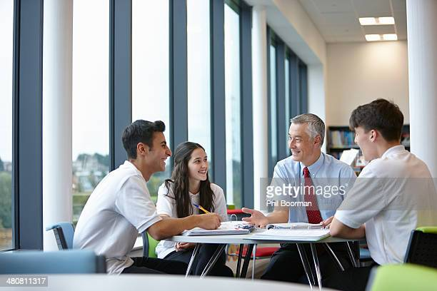 Group of teenagers working with teacher in school class