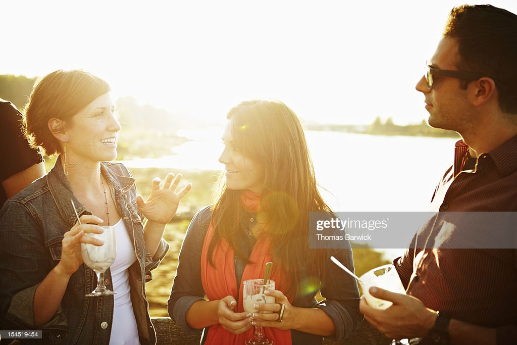 Group of three friends standing on dock at sunset : Foto de stock