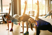 Group of three people workout in healthy club. Young people stretching.