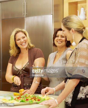 Group of three women preparing food and smiling