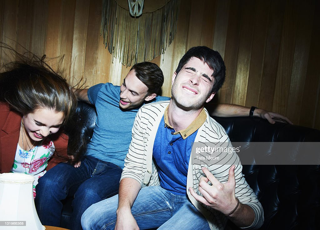 group of three young adults doing air guitar