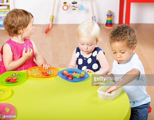 Group Of Toddlers Having Healthy Snack In A Nursery Setting