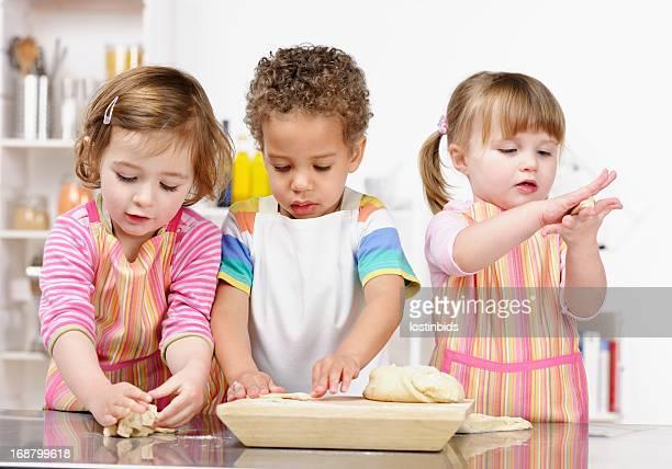 Gruppe von Babys/kleine Kinder spielen mit den Teig vorbereiten /