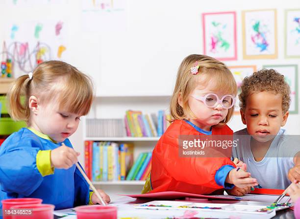 Group Of Toddlers Painting In A Nursery Setting