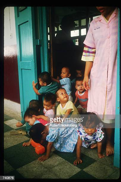 A group of toddlers play inside a doorway at the Phyathai Baby Home January 26 1987 in Bangkok Thailand Fewer than thirty percent of orphaned...