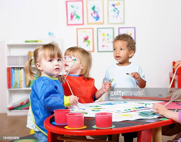 Group Of Toddlers/ Pre Schoolers Painting In A Nursery Setting