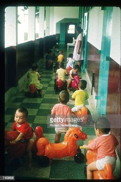 A group of toddlers ride toy horses down a hallway at the Phyathai Baby Home January 26 1987 in Bangkok Thailand Fewer than thirty percent of...