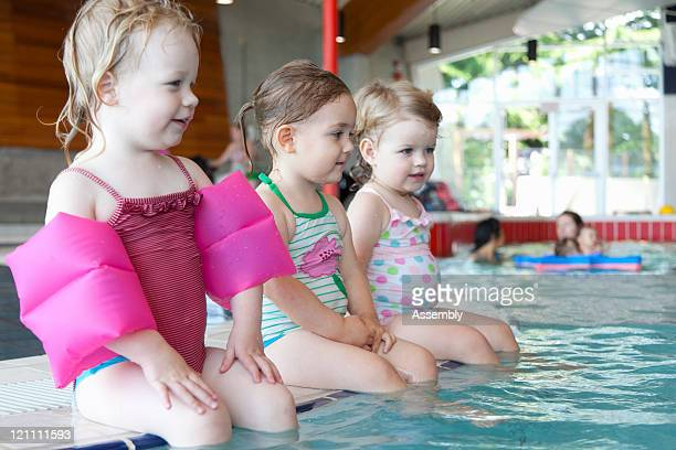 Group of toddlers sitting on edge of pool