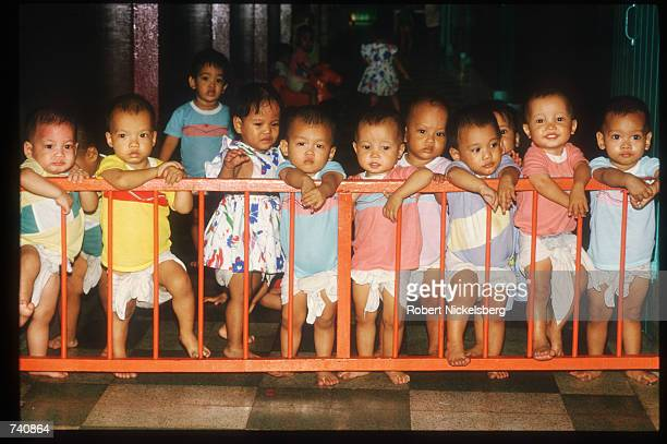 A group of toddlers stand behind a fence at the Phyathai Baby Home January 26 1987 in Bangkok Thailand Fewer than thirty percent of orphaned children...