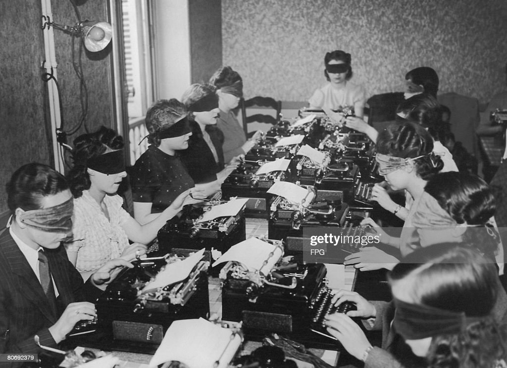 A group of touch typists taking part in a competition while wearing blindfolds, Paris, 25th June 1939.