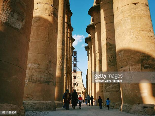 Group Of Tourist Walking By Large Columns Of Luxor Temple