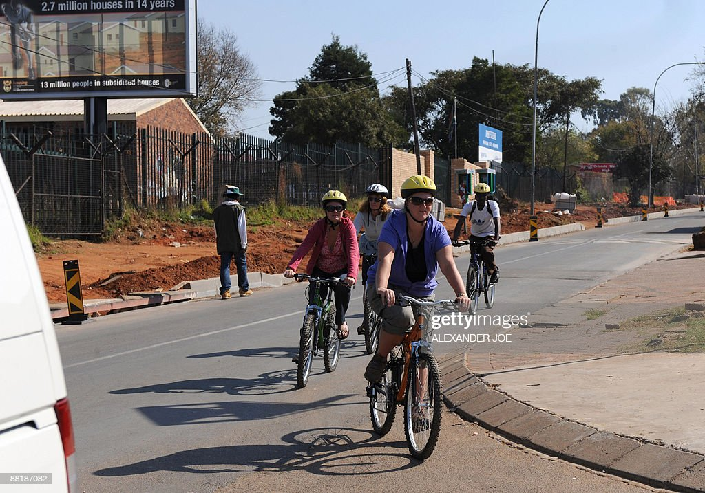 A group of tourists are pictured during a bicycle tour of Soweto township on the outskirts of Johannesburg South Africa on May 20 2009 Long...