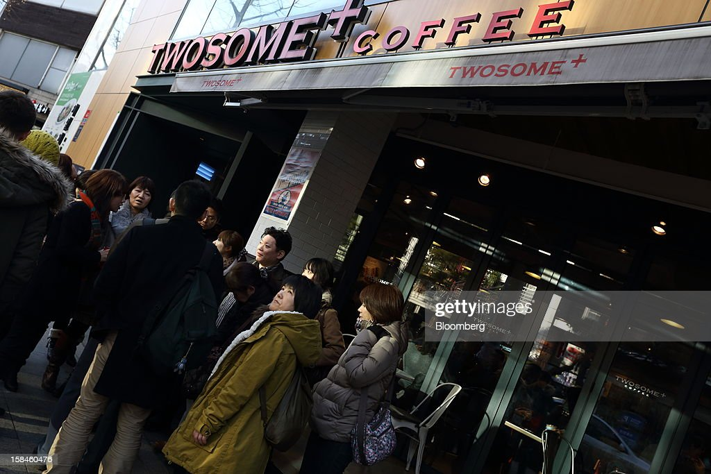 A group of tourists from Japan stand in front of a coffee shop on Garosugil street in the Gangnam district of Seoul, South Korea, on Saturday, Dec. 15, 2012. South Koreans vote on Dec. 19 to replace President Lee Myung Bak, whose five-year term ends in February. Photographer: SeongJoon Cho/Bloomberg via Getty Images