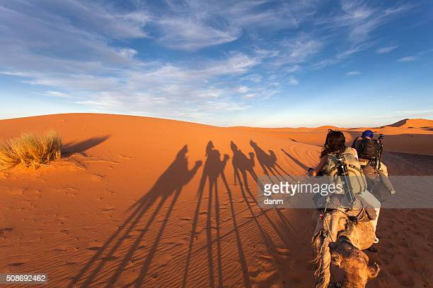 Group of tourists going for a caml trip in the middle of deserts with old nomads