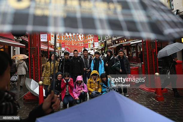 A group of tourists have their photograph taken in the rain in China Town on January 30 2014 in London England The Chinese Lunar New Year of Horse...