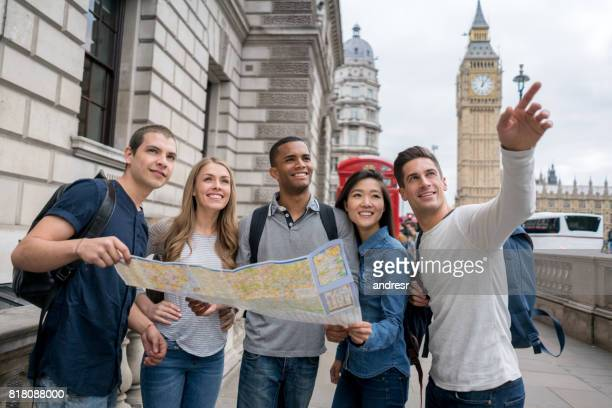 Group of tourists in London holding a map and pointing away