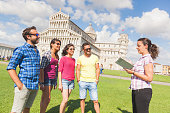 Group of tourists in Pisa, Italy. A group of friends is listening to a guide talking about a famous monument. They are two women and two men wearing summer clothes. They are a multicultural group on h