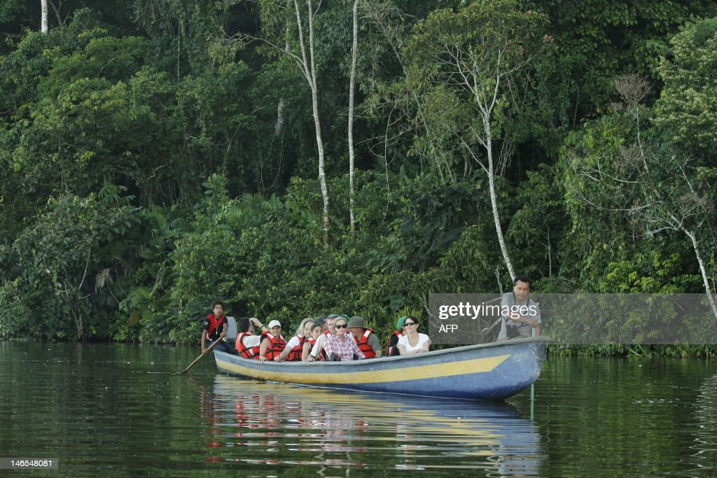 A group of tourists is seen on a boat at the Limoncoha lake, next to the Yasuni Ecuadorean National Park, in the Orellana Province,Ecuador, on June 16, 2012. The Yasuni National Park contains Ecuador's largest oil reserves, but its exploitation would imply impacts to pristine ecosystems, particularly watersheds. In 2007, the government of Rafael Correa offered the proposal of not allowing extraction of the Ishpingo-Tambococha-Tiputini (ITT) oil fields in Yasuni, if the world community compensates to leave the oil permanently in the ground.Ecuador will propose at the Rio+20 summit the environmental project, launched in 2010 to prevent the extraction of 846 million barrels of crude oil from the Amazonian Yasuni rainforest, after the country obtained a contribution from international donors of 116,9 million US dollars this first year. AFP PHOTO/Pablo COZZAGLIO