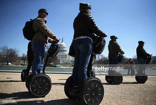 A group of tourists join a Segway tour for sightseeing as they pass in front of the US Capitol on the first day of spring March 20 2014 in Washington...