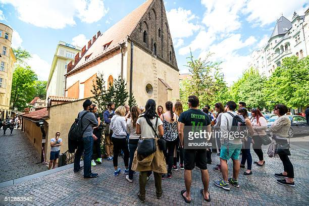 Group of tourists listening to guide on Prague street