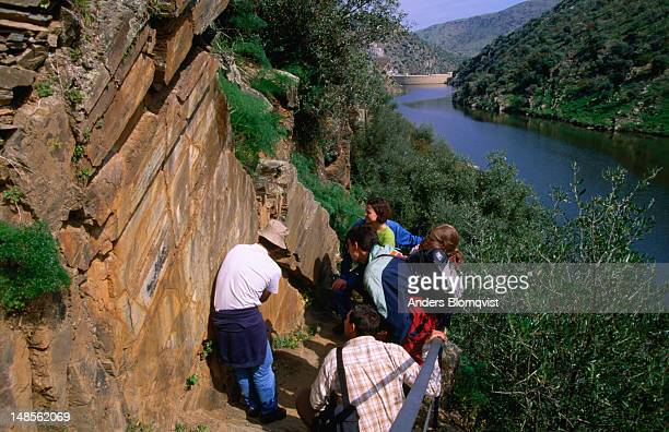 Group of tourists looking at Paleolithic rock engravings on Roca 14, Canada do Inferno, Parque Arqueologico Vale do Coa.