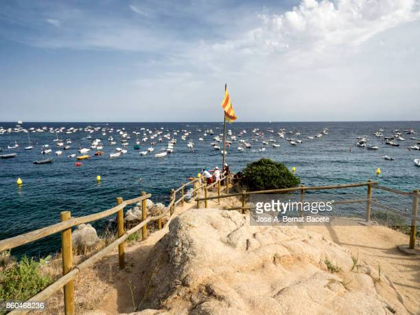 A group of tourists next to a flag of Catalonia on a lookout by the sea. Viewpoint on the Costa Brava in the village of Calella. Catalonia, Spain.