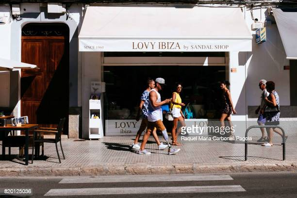 Group of tourists one of them with orthopedic leg walking by fashion shop in 'Vara de Rey' promenade