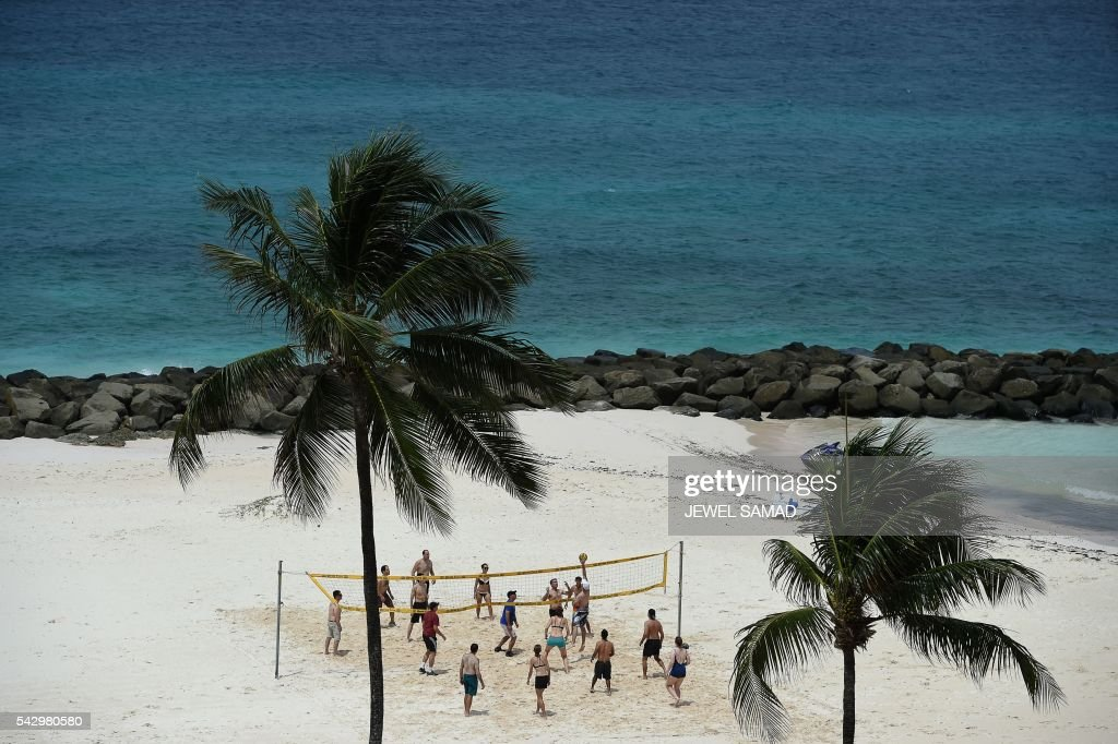 A group of tourists play beach volleyball in Barbados on June 25, 2016. / AFP / Jewel SAMAD